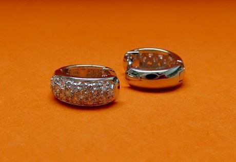 """Picture of """"Pavé"""" huggies, hinged earrings in sterling silver inlaid with round cubic zirconia on the front side"""