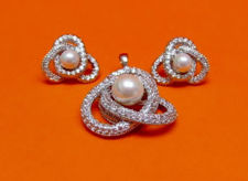 "Picture of ""Pearl on Love Knot"" set of pendant and stud earrings in sterling silver, a single cultured pearl framed by a love knot of round cubic zirconia"