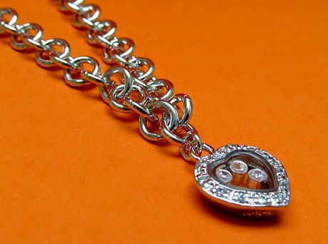 """Picture of """"Playful"""" bracelet in sterling silver, rolo link chain with heart charm outlined with cubic zirconia and containing floating zirconia"""