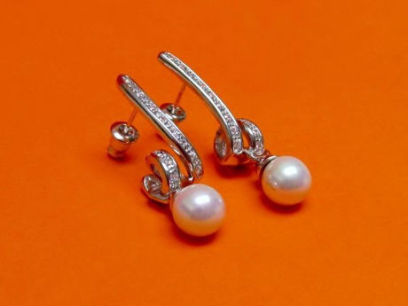 "Picture of ""Spiral and pearl"" dangle earrings in sterling silver, a single cultured pearl dangling from a spiral inlaid with round cubic zirconia"