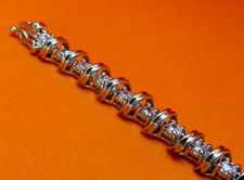 "Picture of ""Spiraling in Zirconia "" tennis bracelet in sterling silver, a row of prong set round cubic zirconia interspersed with spiraling waves"